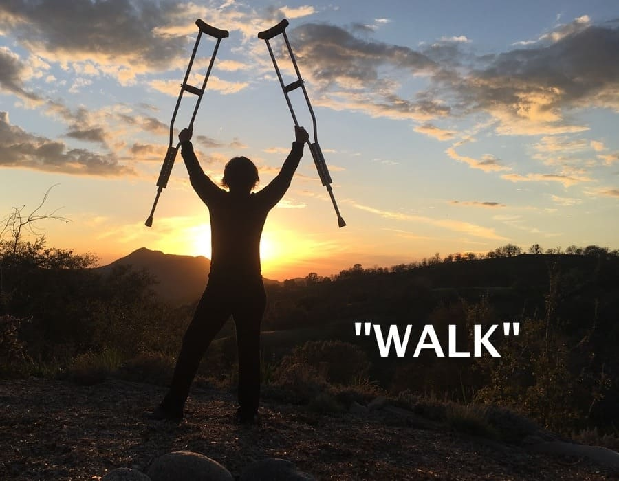Amanda holding crutches up into the sky, at sunset