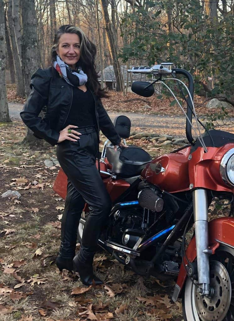 Maria, half her size, at about 128 pounds, standing in front of a red motor cycle wearing black leather pants and a black leather jacket.