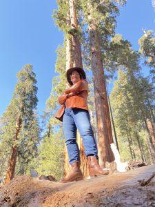 Amanda Rose standing under Giant Sequoia trees
