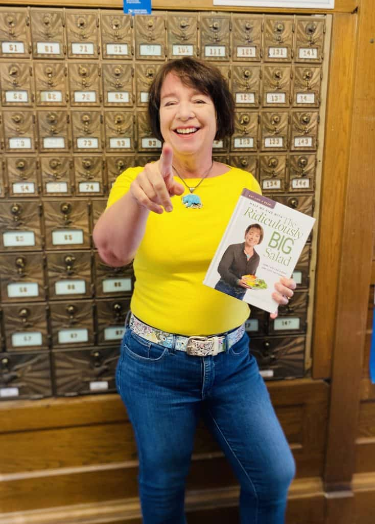 "Amanda Rose in the post office holding the book ""Half My Size with The Ridiculously Big Salad"""