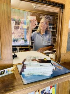 Postmaster Sandy waving through the plexiglass at this small post office.