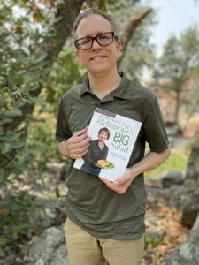 "Sander holding the book, ""Half My Size with The Ridiculously Big Salad."""