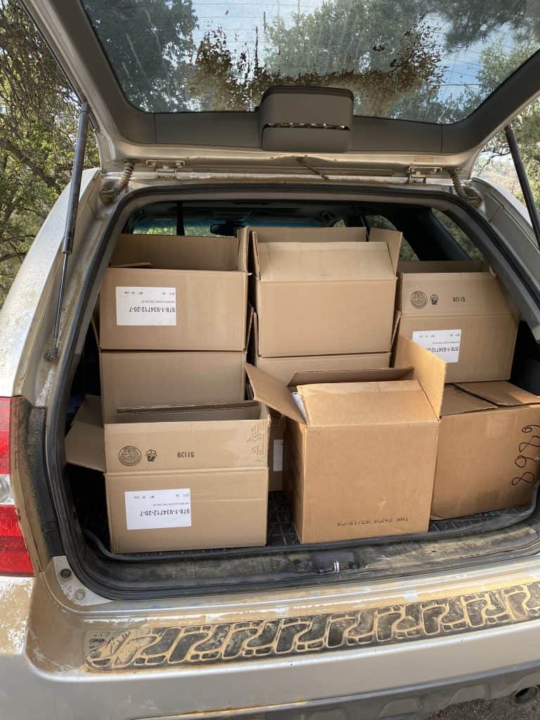 The back of an SUV opened, displaying boxes of books headed to the post office.