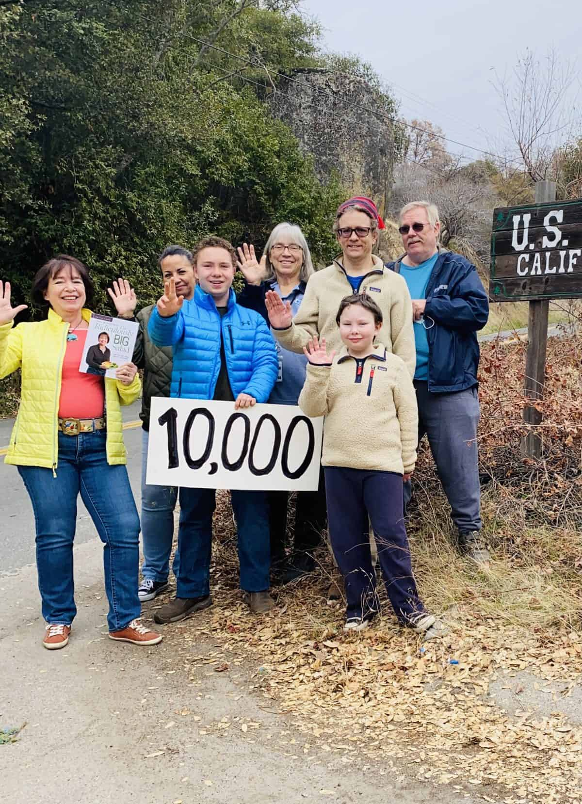 """Amanda Rose and the team that helped her ship 10,000 books, holding a sign that says """"10,000)"""